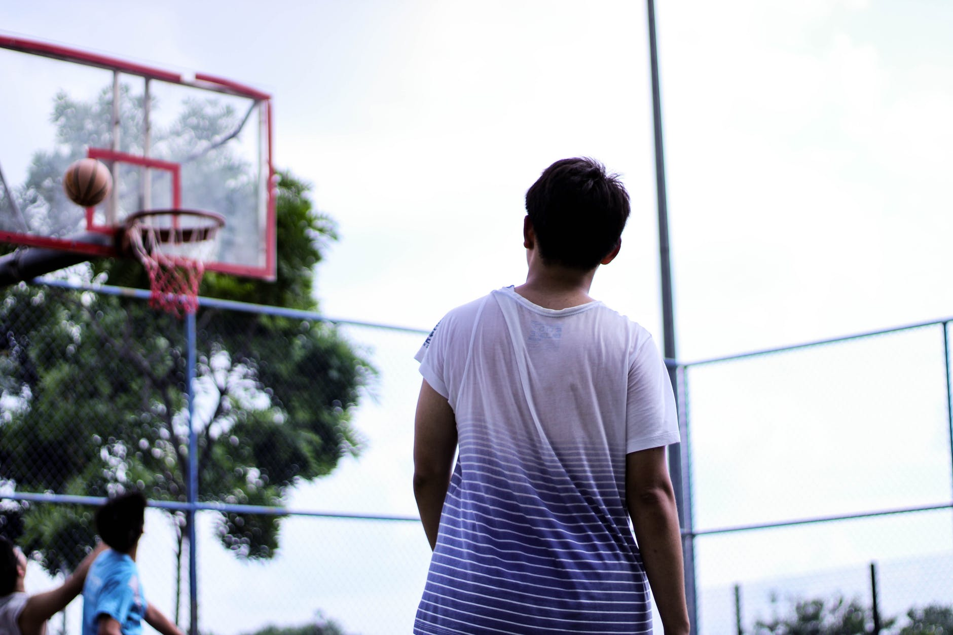 man standing near red basketball hoop system